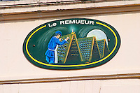 A painted sign that illustrates the theme of champagne and wine production: Le Remueur - the riddler of the bottles in a vaulted cellar with pupitres, the village of Hautvillers in Vallee de la Marne, Champagne, Marne, Ardennes, France
