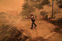 Pictured: A local resident uses buckets of water to try and keep the flames at bay outside his house at the village of Gouves in northern Evia siland, Greece. Sunday 08 August 2021<br /> Re: Forest fire in northern Evia, Greece.