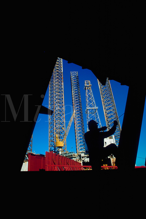 Silhouette of worker with measuring tape in front of jackup oil rig repair facility