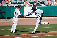 Johan Lopez (32) of the Charleston RiverDogs shakes hands with third base coach Blake Butera (3) after hitting a home run against the Augusta GreenJackets at Joseph P. Riley, Jr. Park on June 27, 2021 in Charleston, South Carolina. (Brian Westerholt/Four Seam Images)