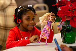 WATERBURY, CT. 21 December 2019-122119BS292 - Rayanna Foote, 7, of Waterbury plays with her barbie doll to pass the time, during a Christmas Party for the less fortunate and homeless at the Basilica of Immaculate Conception in Waterbury on Saturday. Bill Shettle Republican-American