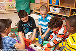Education preschool 4-5 year olds group playing together with blocks toy furniture setting up scene