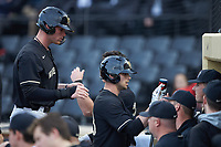 Jake Mueller (23) of the Wake Forest Demon Deacons high fives teammates after scoring a run during the game against the Notre Dame Fighting Irish at David F. Couch Ballpark on March 10, 2019 in  Winston-Salem, North Carolina. The Fighting Irish defeated the Demon Deacons 8-7 in 10 innings in game two of a double-header. (Brian Westerholt/Four Seam Images)