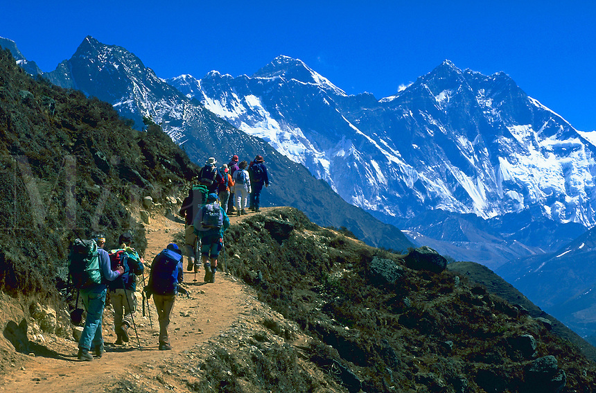 A group of climbers on a path beneath Mount Everest that rises just over Nuptse, Khumbu Himalaya, Nepal.
