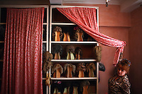 A hair stylist lifts a curtain revealing stored wigs inside a dressing room in the Tiraspol Theater in Tiraspol, Transnistria on 11 April 2009.