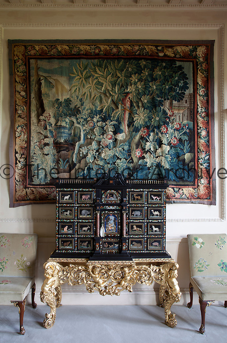 An antique kunst cabinet in the drawing room, elaborately inlaid with animals made of different materials