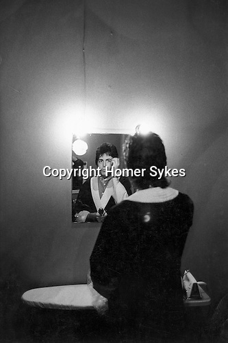 """Paul and Linda McCartney Wings Tour 1975. Paul in dressing room  fixing hair in mirror before going on stage. Bristol, England. The photographs from this set were taken in 1975. I was on tour with them for a children's """"Fact Book"""". This book was called, The Facts about a Pop Group Featuring Wings. Introduced by Paul McCartney, published by G.Whizzard. They had recently recorded albums, Wildlife, Red Rose Speedway, Band on the Run and Venus and Mars. I believe it was the English leg of Wings Over the World tour. But as I recall they were promoting,  Band on the Run and Venus and Mars in particular."""