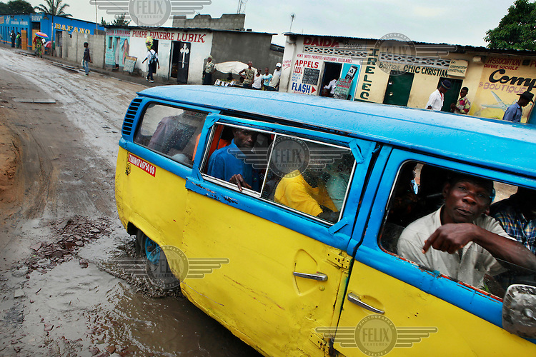 A public bus makes its way along a flooded road in Kimbanseke...