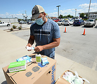 """Doug Allen, owner of Jose's Bar and Grill, collects items Friday, Aug. 21, 2020, as he hands out boxes of personal protective equipment to Northwest Arkansas teachers at the restaurant in Tontitown. Allen raised about $13,000 to provide hand sanitizer, masks and cleaning supplies for teachers. """"We've got an assortment of stuff for them to help them outfit their classroom, put their mind at ease and let the community know we care about our teachers,"""" Allen said. Visit nwaonline.com/200823Daily/ for today's photo gallery.<br /> (NWA Democrat-Gazette/Andy Shupe)"""