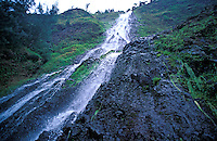 A beautiful waterfall cascades down the lush mountainside in Waipio Valley on the Big Island of Hawaii.