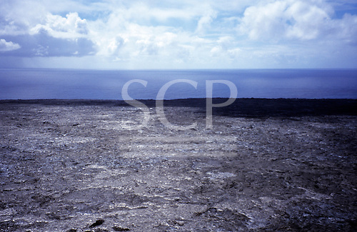Big Island, Hawaii. Aerial view of lava field shining silver in sun with ocean beyond.