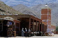 Men shaking hands outside a mosque in the Atlas Mountains, Morocco.