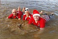 Pictured: A family in Santa outfits dive in. Tuesday 26 December 2017<br /> Re: Hundreds took part in this year's Boxing Day Walrus Dip which see people in fancy dress taking to the sea at Cefn Sidan beach in Pembrey Country Park, west Wales, UK.