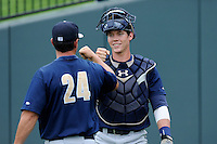 Catcher Peter O'Brien (9) of the Charleston RiverDogs bumps fists with coach Justin Tordi (24) before a game against the Greenville Drive on Sunday, May 19, 2013, at Fluor Field at the West End in Greenville, South Carolina. O'Brien was a second-round pick of the New York Yankees in the 2012 First-Year Player Draft. Charleston won, 9-7. (Tom Priddy/Four Seam Images)