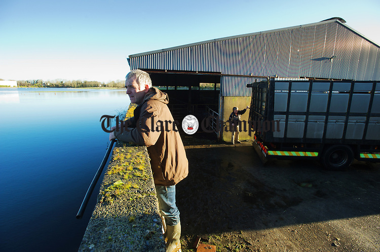John Nolan watches the flooding as it rises over his farm at Corker, Kiltartan. In the background, haulier Michael Lynskey locks up John's cattle in a truck for evacuation from the slatted house before the water comes in. Photograph by John Kelly.