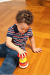 Toddler boy age 18 months at home playing with ring and spindle toy