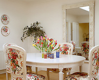 A large mirror against one wall of the dining area reflects the simple white table and four chairs upholstered in a floral print