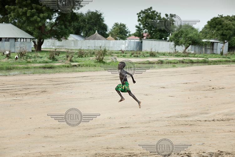A boy runs across an unpaved road in Malek village.