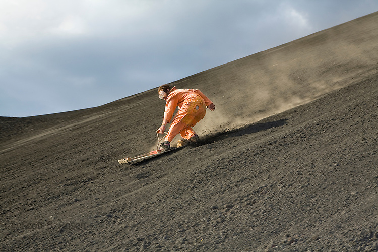 Man stands on his volcano board for part of his decent down the active Volcano Cerro Negro, Nicaragua
