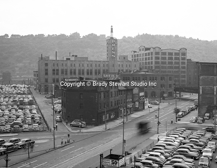 Pittsburgh PA:  View of the point area prior to the Gateway Center construction.  Eppy's parking lot at Liberty Avenue and Fourth Avenue in Pittsburgh.  Pittsburgh Press Building in the background.  Company signs on the city buildings include:  Esser Costume Company, Amaco Service Station, and Follansbee Steel Corporation