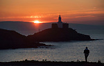 Swansea, UK, 25th March 2020.<br />Sunrise over the Mumbles Lighthouse near Swansea today as government warnings continue to ask people to stay at home due to the Coronavirus outbreak in the UK.