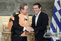 Pictured L-R: Ban Ki-Moon is given one of the used life vests used by migrants to cross the Aegean sea, by Greek Prime Minister Alexis Tsipras at Megaro Maximou in Athens, Greece. Saturday 18 June 2016<br /> Re: The United Nations secretary-general is visiting Greece, ahead of talks with government officials and a trip to the island of Lesbos, which is at the forefront of Greece's immigration crisis.<br /> Ban Ki-moon met with officials and volunteers at the Solidarity Now group, which helps victims of Greece's financial crisis and migrants stuck in the country.<br /> He has also visited Greek President Procopis Pavlopoulos before travelling camps on Lesbos island where 3,400 refugees and other migrants live.