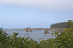 View of the rugged entrance to the Umpqua River and diminutive Umpqua River Lighthouse from Cape Arago on the Central Oregon Coast with views of Sunset State Park and the Umpqua River Lighthouse, and massive headlands. Near Coos Bay, Oregon, Cape Arago is known for its rugged views, hiking, wildlife, beach access, and Sunset Beach State Park and unique geology.