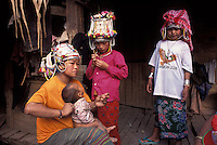 Laos, Luang Namtha Province, Ban Nammat Gao village, 12/3/03..Akha family together after work at the end of the afternoon. The women and girls are wearing the traditional head-dress, which takes a lot of work to maintain. Photo Kees Metselaar