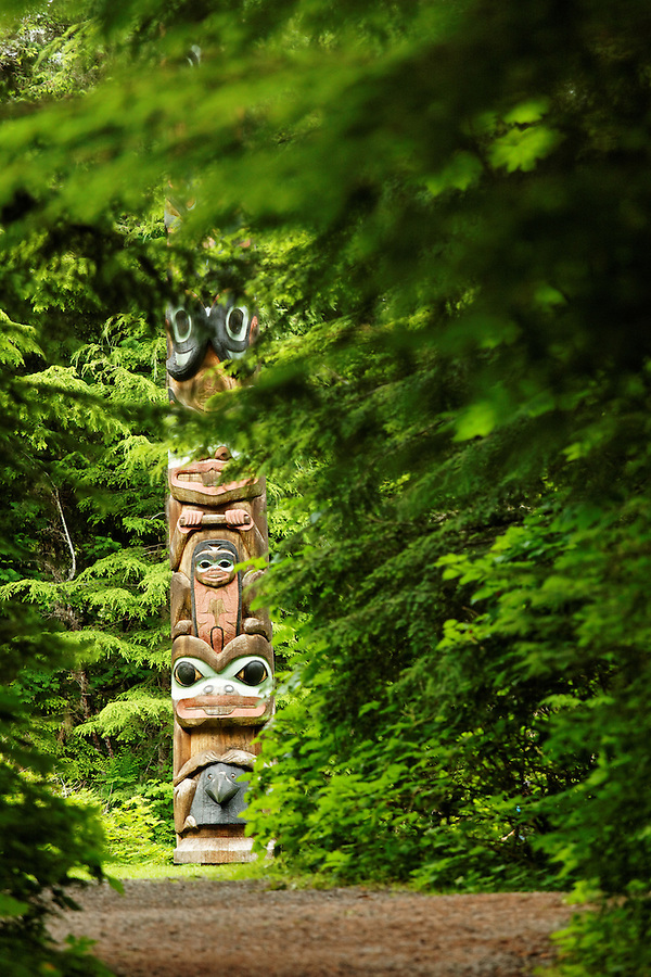 Base of K'alyaan Pole seen down trail through forest, Sitka National Historical Park, Sitka, Alaska, USA