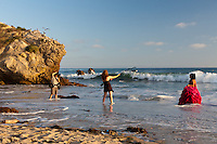 A young woman in a red dress stands in the ocean while a photographer takes pictures of her and an assistant holds a remotely activated flash.  The poor young woman (and her dress) was getting soaked.  This was taken at the south/east end of Corona Del Mar State Beach, just below Inspiration Point.
