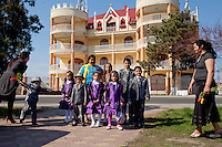 The Bureata and Stan families pose for a portrait on the Friday before Easter, in which traditionally everyone brings flowers to the church. Buzescu is known for it's ultra-wealthy Roma and their bizarre mansions that line the main street. The Roma of Buzescu are part of the Kalderash clan and are known for being coppersmiths and dealing with metal scraps. After the fall of the communist regime in the late 80's, they stripped old factories of their metals and some made a small fortune re-selling them. They are also known for making cazane, copper stills that produce alcohol such as palinka, a plum brandy.