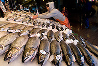 A worker arranges salmon at Pike Place Market in Seattle Washington.