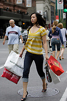 Montreal (Qc) CANADA, July 24, 2007 - Model Released photo- A young asian woman carrries a handfull of bags while shopping on Sainte-Catherine street West in Downtown Montreal.<br />