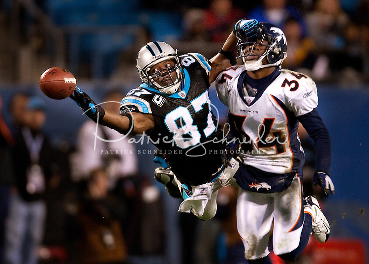 Carolina Panthers wide receiver Muhsin Muhammad (87) dives for a pass against Denver Broncos cornerback Josh Bell (34) during an NFL football game at Bank of America Stadium in Charlotte, NC.