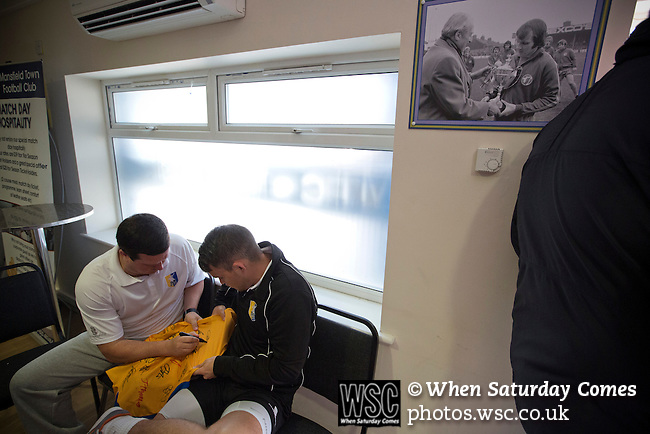 Mansfield Town Football Club Open Day, 14/07/2013. Field Mill stadium, League Two. Current Mansfield Town manager PaulCox (left) signing a shirt for a fan in the Sandy Pate Lounge at Field Mill stadium (overlooked by a 1975 photo of Sandy Pate receiving the Fourth Division trophy) during an open day held for the club's supporters. Mansfield Town achieved promotion back to England's Football League by winning the Conference National in season 2012-13. Field Mill was the oldest ground in the Football League, hosting football since 1861 although some reports date it back as far as 1850, with Mansfield Town having played there since 1919. Photo by Colin McPherson.