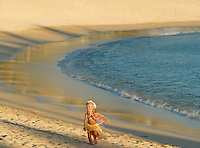 Young girl visiting the islands wearing a hula skirt and dancing on the beach