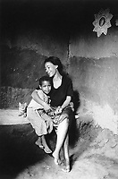 Ethiopia. West Gujam. Danbecha district. Anjeni is a small village. A cat seats close to two sisters holding each other in their arms. The walls of the house are made of mud. © 1996 Didier Ruef