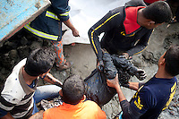 Bangladeshi rescue workers carry the body of a victim of a ferry capsize during a rescue operation in the River Padma Sunday after being hit by a cargo vessel at Paturia , in Manikganj district, about 80 kilometers  northwest of Dhaka, Bangladesh. Feb. 23, 2015.
