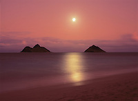 Sunset colors enhance a full moon rising between the Mokulua Islands off of Lanikai Beach, Oahu, Hawaii.