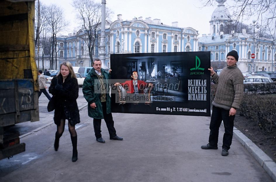 Europe-Asie/Russie/Saint-Petersbourg: Monastère de Smolny - Hommes portant une affiche publicitaire pour des meubles représentant Dali