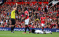 Pictured L-R: Match referee Mike Dean shows Tyler Blackett of Manchester United a yellow card for his foul on Bafetimbi Gomis of Swansea. Saturday 16 August 2014<br /> Re: Premier League Manchester United v Swansea City FC at the Old Trafford, Manchester, UK.