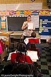 K-8 Parochial School Bronx New York Grade 4 female teacher  talking to class holding up paper vertical