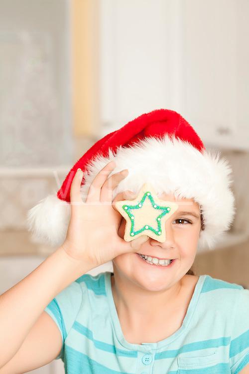 USA, California, Lawndale, Portrait of girl (10-11) wearing santa hat holding cookie