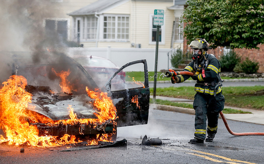 MANASQUAN, NJ — April 1, 2016 —Manasquan firefighter Kevin McCredie works on scene where a 2000 Ford Focus became fully engulfed in flames at about 9:40am on Broad Street, here.   photo by Andrew Mills