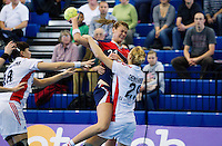 22 OCT 2011 - LONDON, GBR - Britain's Kathryn Fudge (#21 / in blue and red) leaps as she tries to shoot past Russia's Olga Chernoivanenko (#29 - white) during the Women's 2012 European Handball Championship qualification match between the two teams at the National Sports Centre at Crystal Palace .(PHOTO (C) NIGEL FARROW)