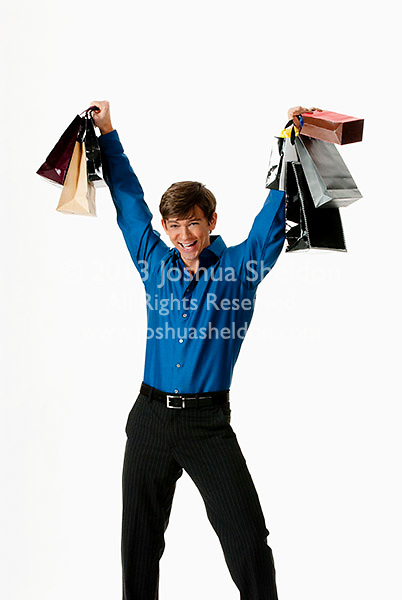 Young man holding shopping bags above his head