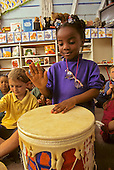 MR/ Schenectady, New York.Yates Arts Magnet School / Pre-Kindergarten.Girl (5, Nigerian-American) with drum as class uses rhythm instruments..MR:Maj1      FC#:23069-00320.scan from slide.©Ellen B. Senisi