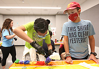 Diego Romero Flores, 10, watches Friday, July 16, 2021, as Seth Alvarez, 11, puts the final dye on his shirt at the Fayetteville Public Library. Children, grades 4 through 8, tie dyed t-shirts during using spiral, sunburst and crumble designs. The dyed shirts were placed in a plastic bag to be taken home and finally rinsed and washed before being worn. Check out nwaonline.com/210717Daily/ and nwadg.com/photos for a photo gallery.(NWA Democrat-Gazette/David Gottschalk)