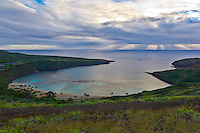 Hanauma Bay in the morning light, with rays from a rising sun beaming through clouds on the horizon, East O'ahu.