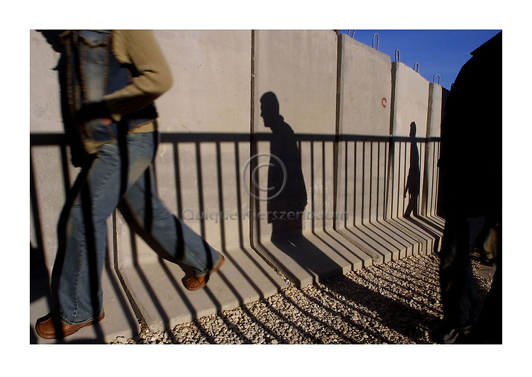 Palestinians walk pass the security wall which separates between the Palestinian neighbor of Abu Dis and Jerusalem. Photo by Quique Kierszenbaum